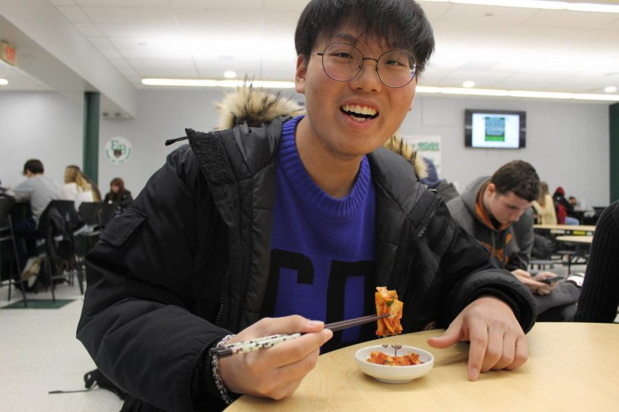 Eric Kim enjoys one of his favorite dishes from South Korea, kimchi.