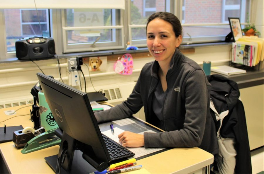 Nurse Brodniak warmly smiles as she works at her computer, staying on top of her work to be prepared for any student or staff member's needs.