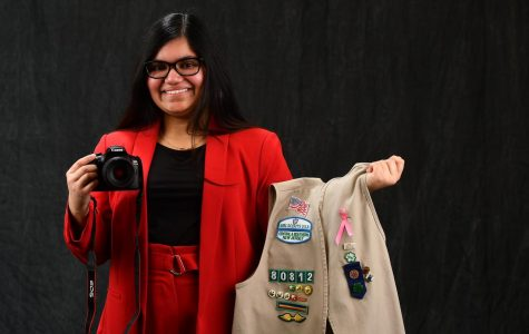Shivani Ghatak, 12, smiles with her camera and Girl Scout vest in hand.