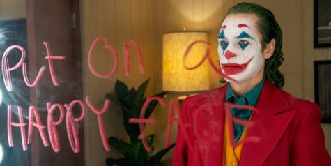 "Joaquin Phoenix as Joker, looks at his reflection through a mirror with part of the famous ""Smile and put on a happy face"" line written on it in red."