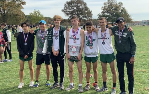 The team's varsity athletes hold a runner-up plaque at the 2019 county championship.