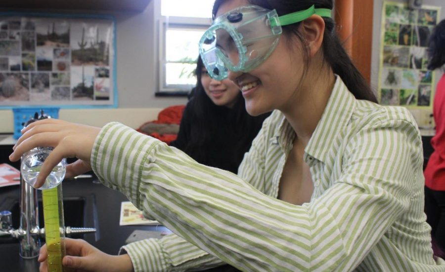 A student measures the amount of liquid as part of a science lab [photo taken before COVID-19]
