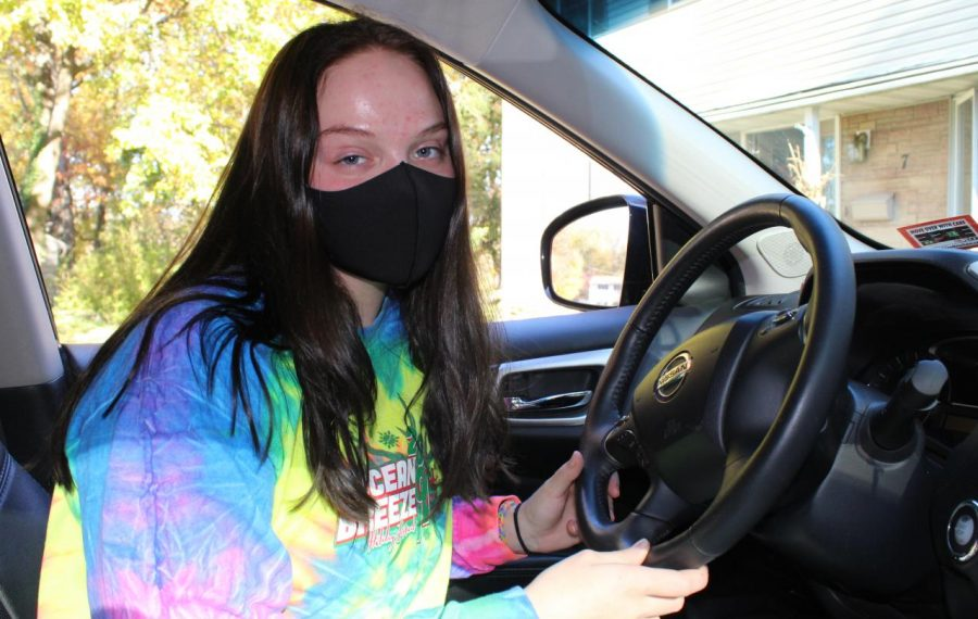 "Cheyenne Swiatkowski, 11, patiently waits at the wheel for her mom. She says, ""My mom always takes so long, and all I want to do is get on the road."""