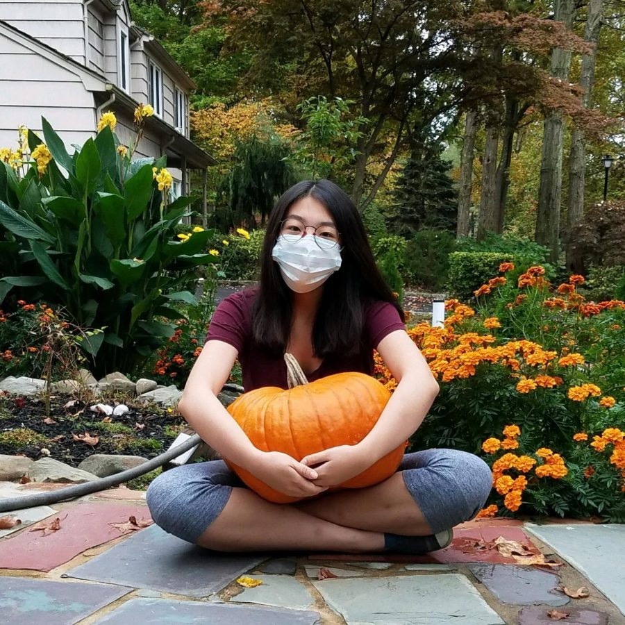Yuntong Li sits cross-legged on a stone path, holding a large pumpkin in her lap.