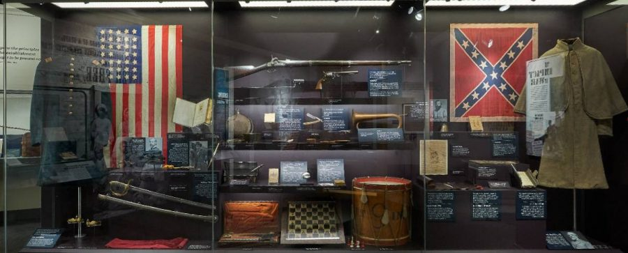 This picture shows items from the militaries of the Civil War. On the left are Union items, like the flag (which can be seen to only feature 36 stars for the 36 states of the time) and an example of their uniform. On the right, there are Confederate items, like an example of their flag and their uniforms. The middle shows items used during the war, like instruments, weapons, and even a sample of hardtack.