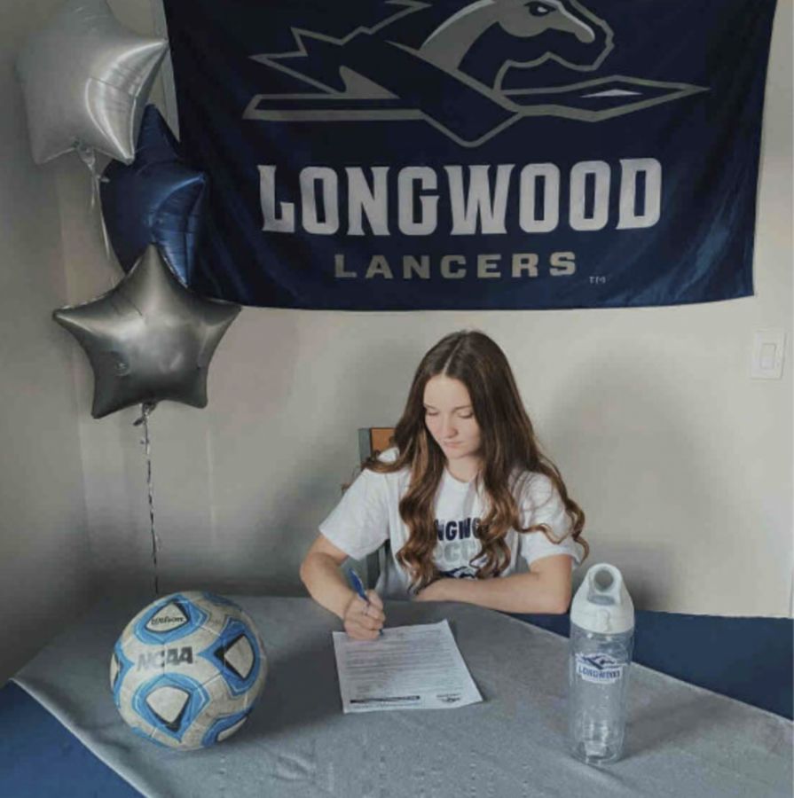 Julia Gill, 12, signs her Letter of Intent to commit to Longwood University.