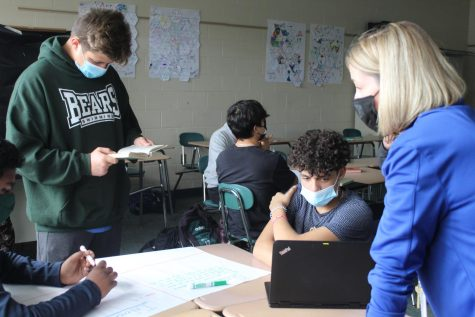 Mrs. Moran enthusiastically joins her students' discussion as they work on a group poster, to help them take their analytic skills to the next level.